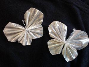 Kaksi perhosta, kierrätysmateriaalista tehdyt heijastavat korut.