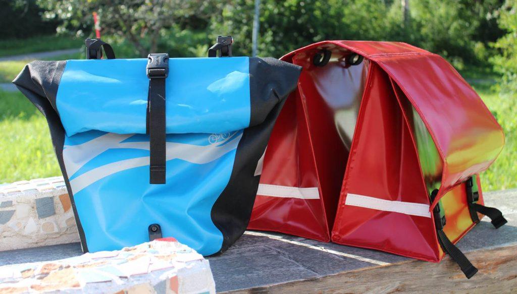 Sininen Ortliebin ja punainen Clarijsin polkupyörän satulalaukku penkillä.