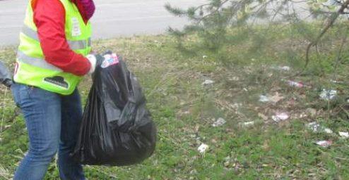 Siivoustalkoot, roskienkerääjä nurmikolla.