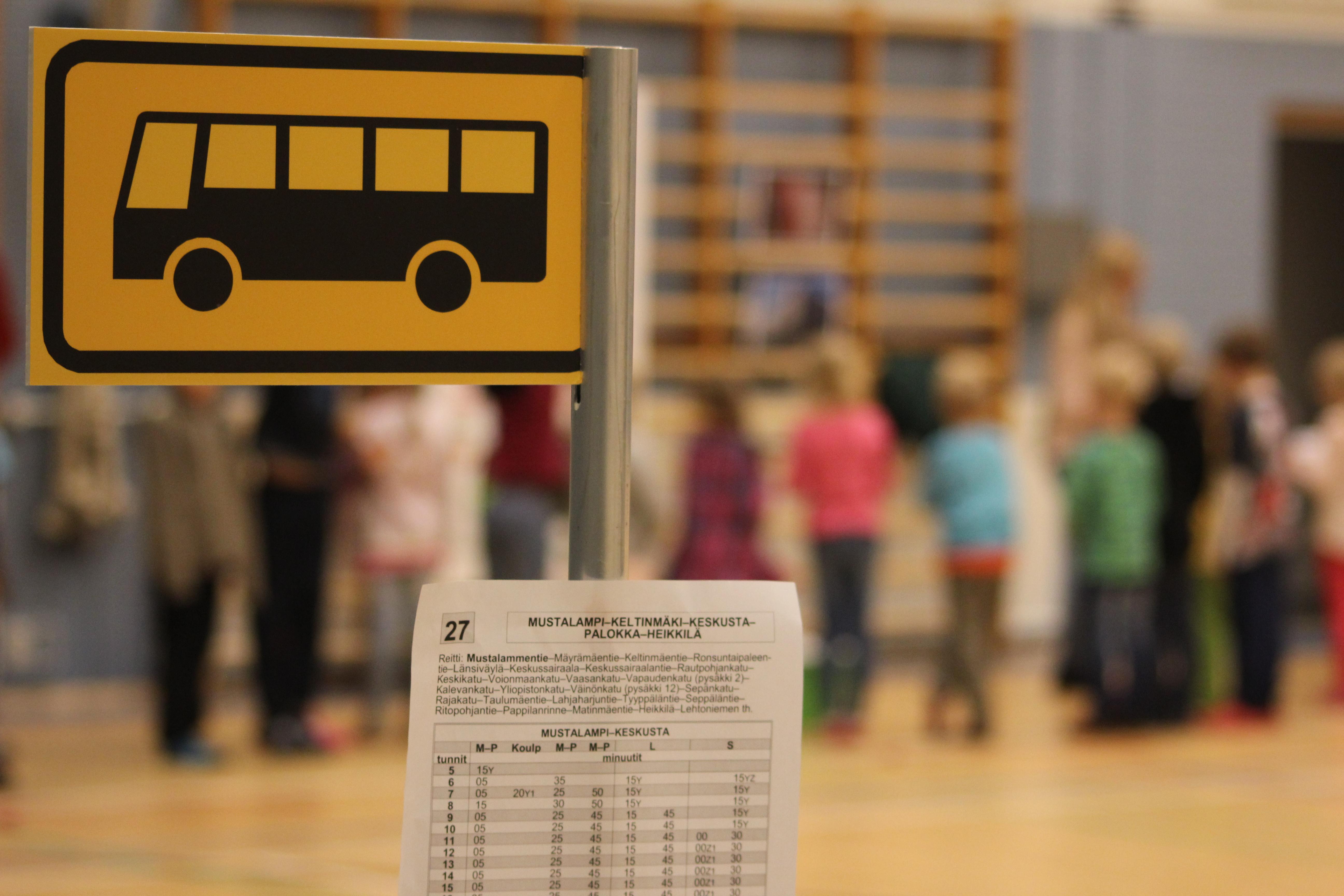 Tuokiokuva Bussiloikka-esityksestä, bussipysäkin merkki etualalla, lapset takana.