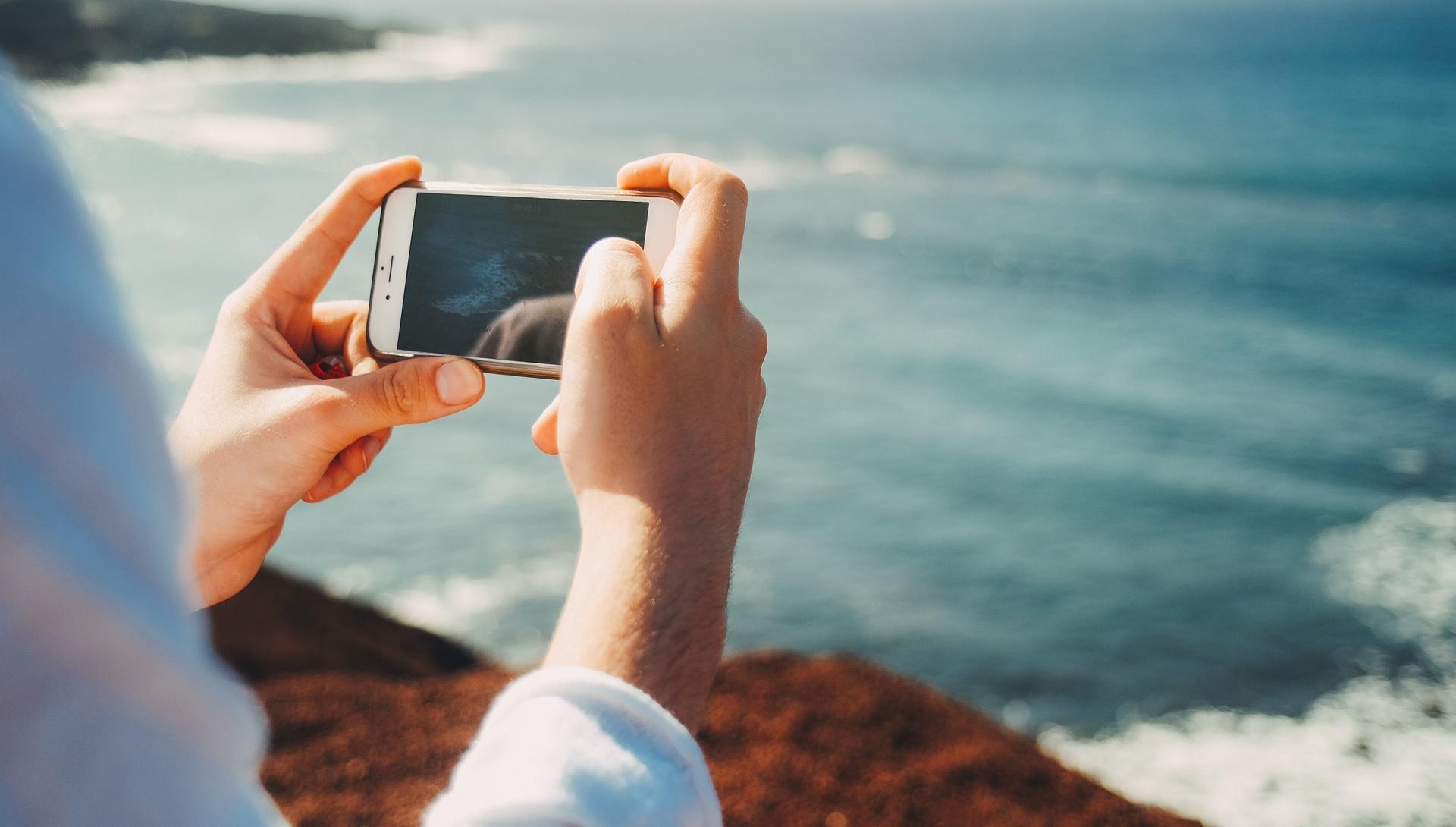 Ihminen ottaa kännykällä kuvan merestä.