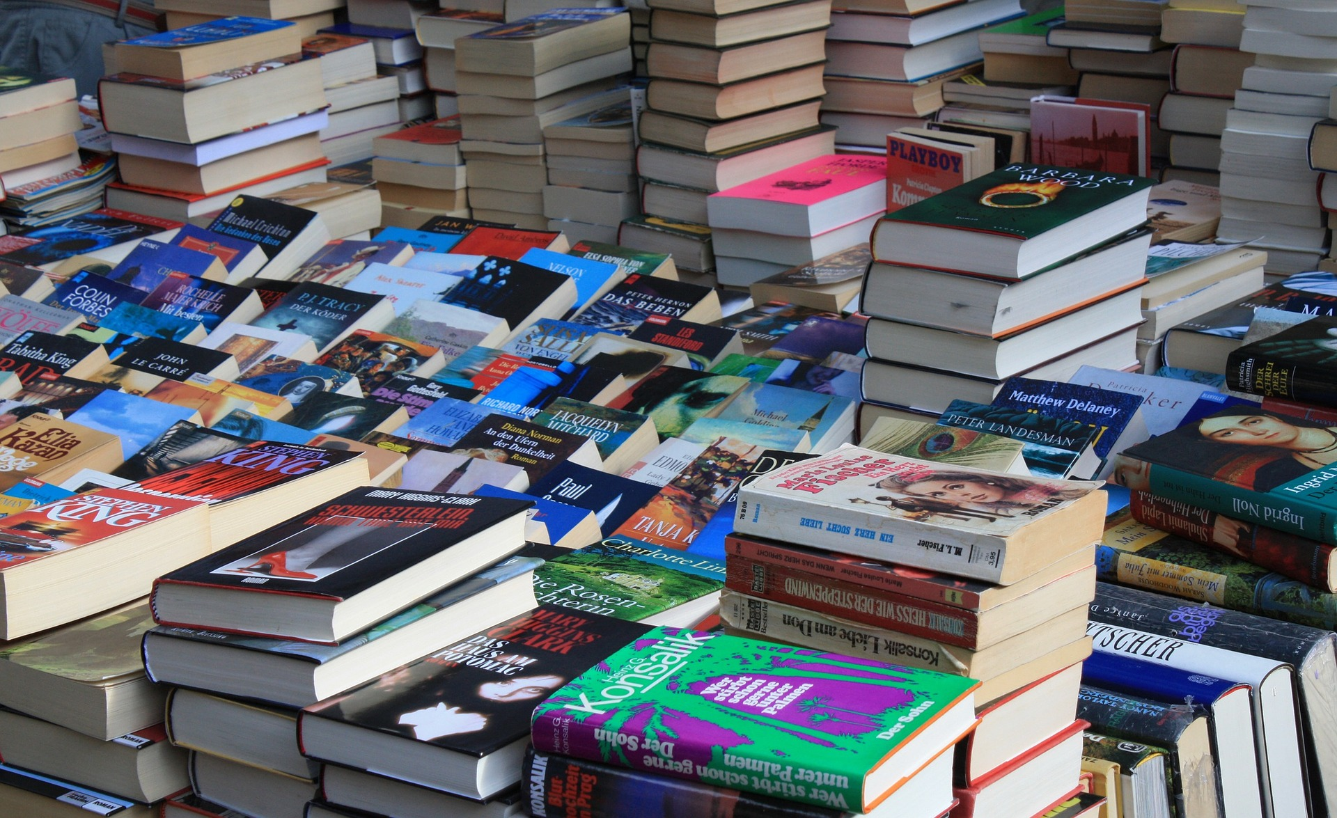 Paljon kirjoja pinoissa pöydällä.