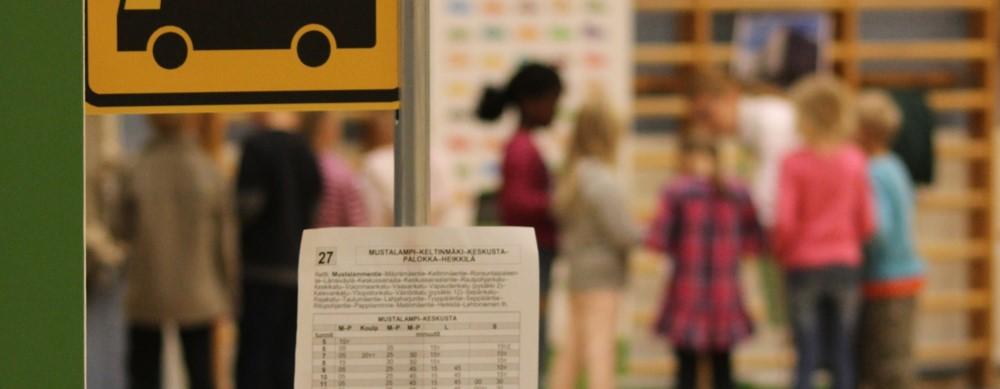 Tuokiokuva Bussiloikkaesityksestä. Edessä bussipysäkin merkki, taustalla eppuluokkalaisia.