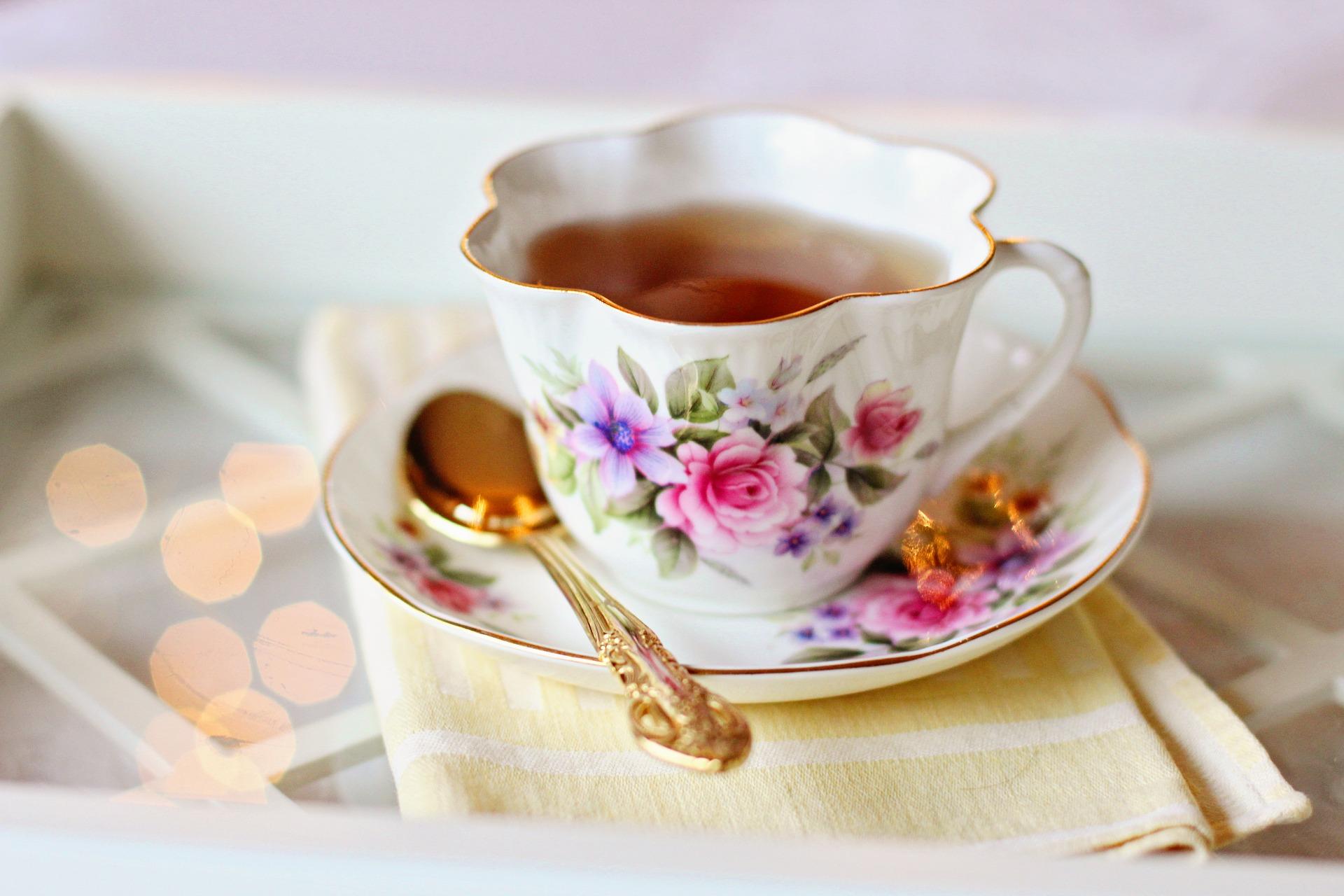 Ruusukuvioinen teekuppi ja tassi, kullanvärinen lusikka.