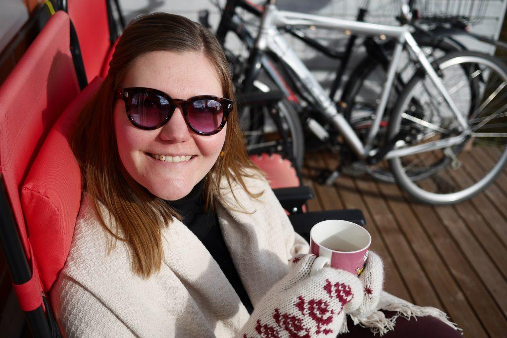 Hymyilevä Netta kahvikuppi kädessä terassituolissa
