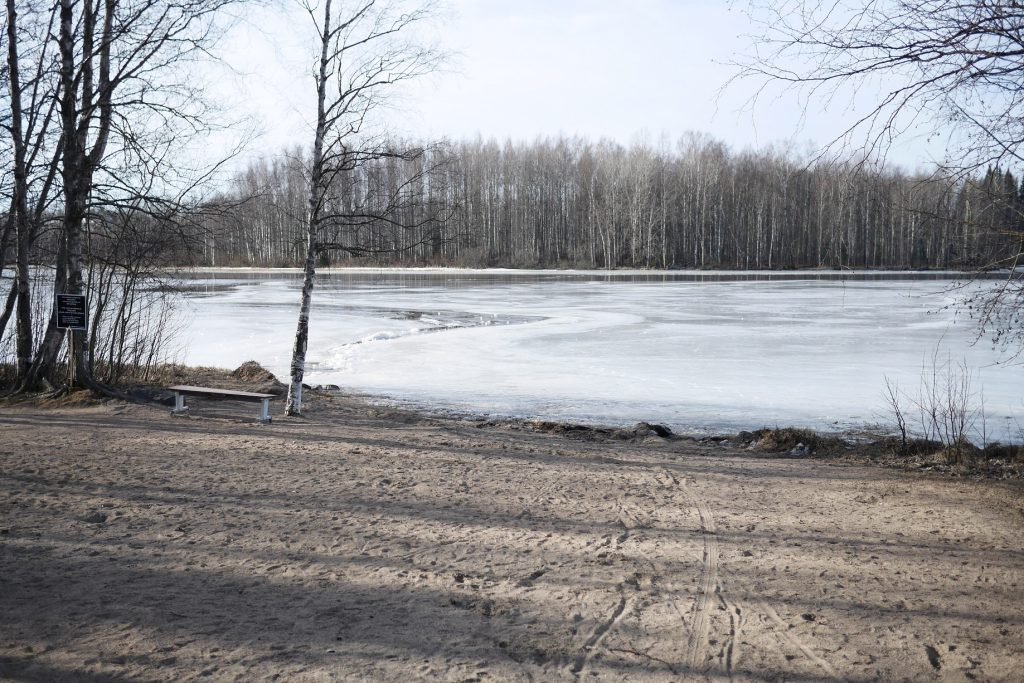 Hiekkaranta ja jäässä oleva järvi