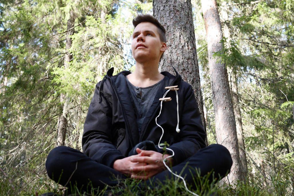 Jyry istuu kivellä metsässä. Handsfree on pyykkipojilla kiinni takissa.
