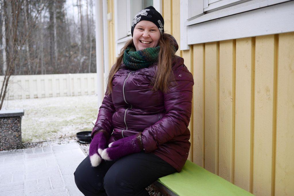 Hymyilevä Johanna istuu penkillä pihassa