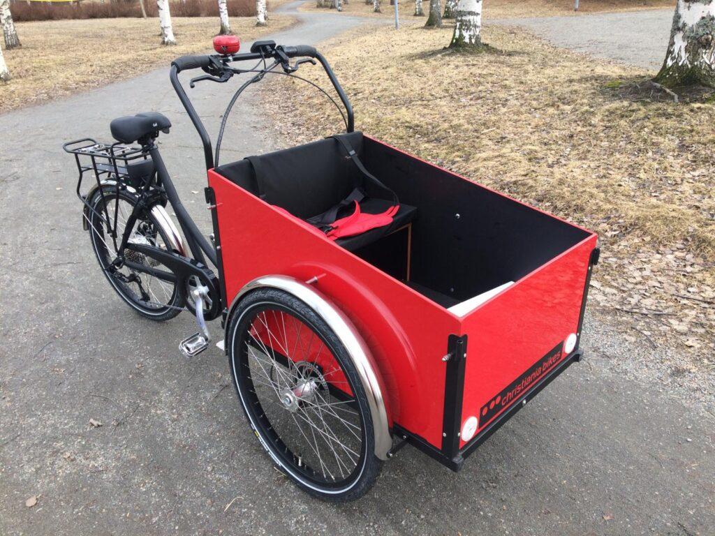 Punainen, kolmipyöräinen, sähköavusteinen Christiania-merkkinen laatikkopyörä.
