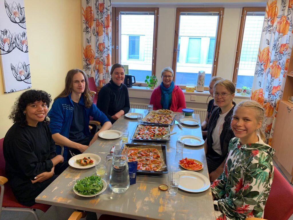 Seitsemän henkilöä pöydän ääressä syömässä