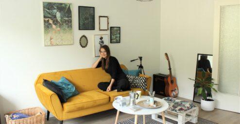 Nuori nainen istuu keltaisella sohvalla vaaleassa olohuoneessa.