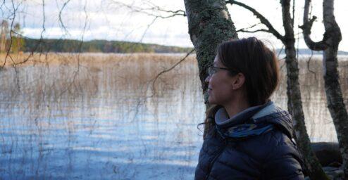 Ihminen nojaa puuhun ja katsoo järvelle.