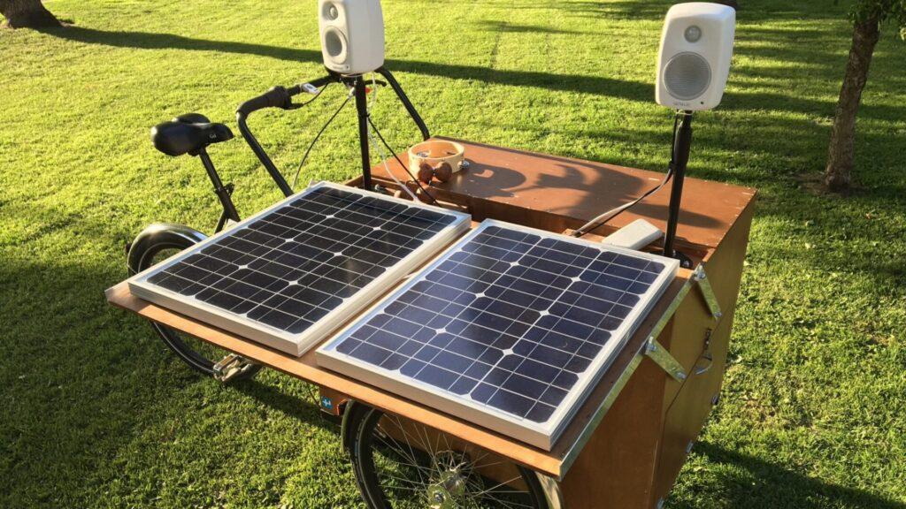 Kolmipyöräinen laatikkopyörä, jossa aurinkokennot, rummut ja kaiuttimet.