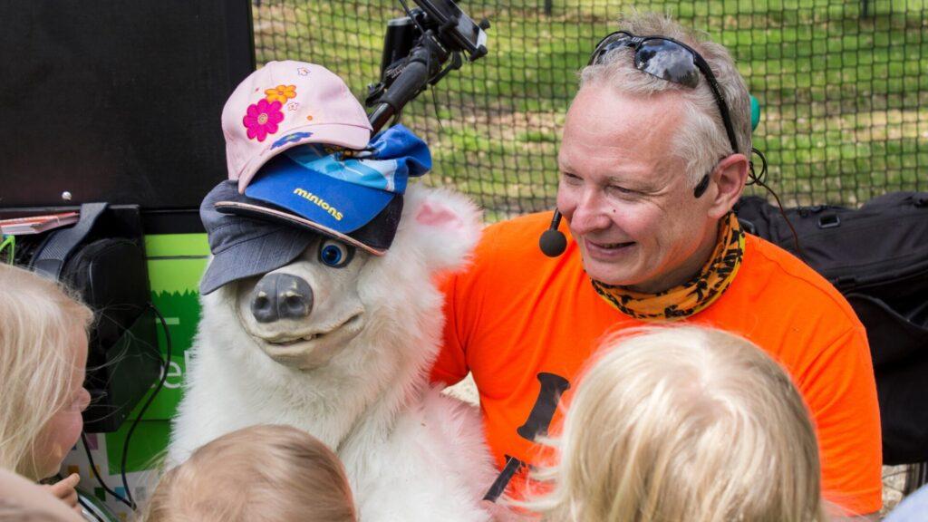 Valkoinen pehmonalle, jonka päässä kolme lasten lippalakkia, mies oranssissa t-paidassa sekä muutama lapsi yleisönä.