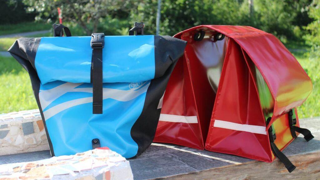 Sininen ja punainen satulalaukku ulkona penkillä.