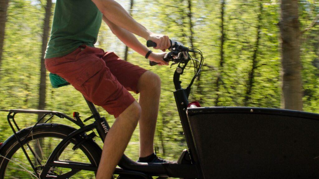 Mies ajaa lastipyörää kesällä, lähikuva.