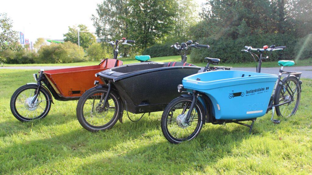 Kolme lastipyörää vierekkäin nurmikolla.